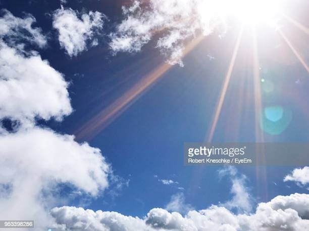 low angle view of vapor trail in sky - sunlight stock-fotos und bilder