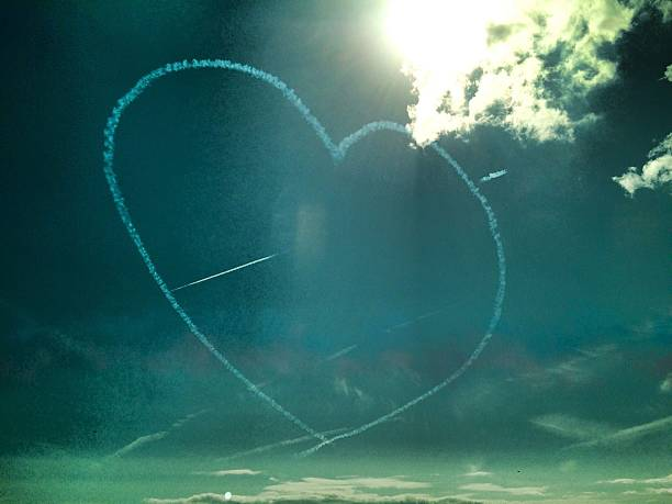 Low Angle View Of Vapor Trails Forming Heart Shape In Sky