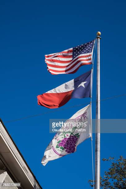 Low Angle View Of Various Flag Against Clear Blue Sky