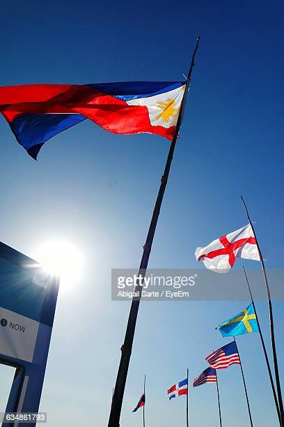 low angle view of various flags against sky on sunny day - filipino flag stock pictures, royalty-free photos & images