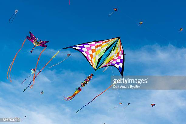 low angle view of various kites flying in sky - kite stock pictures, royalty-free photos & images