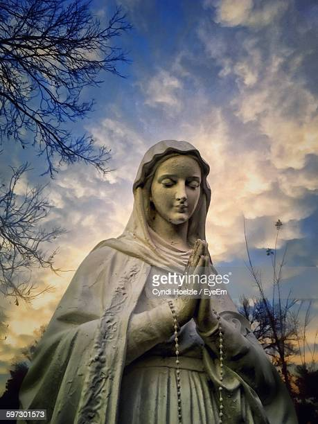 low angle view of virgin mary statue against cloudy sky - la vierge marie photos et images de collection