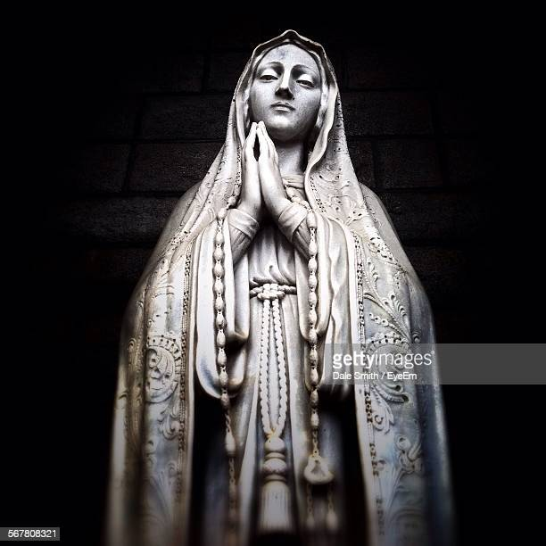 low angle view of virgin mary statue against wall - la vierge marie photos et images de collection