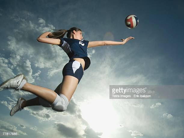 low angle view of volleyball player jumping - volleyball mannschaftssport stock-fotos und bilder