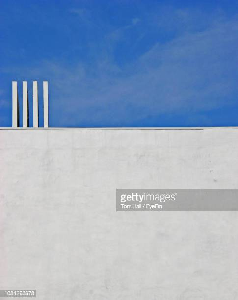 low angle view of wall against blue sky - whitewashed stock photos and pictures