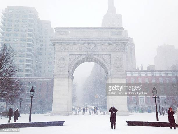 low angle view of washington square arch and buildings in foggy weather - washington square park stock pictures, royalty-free photos & images