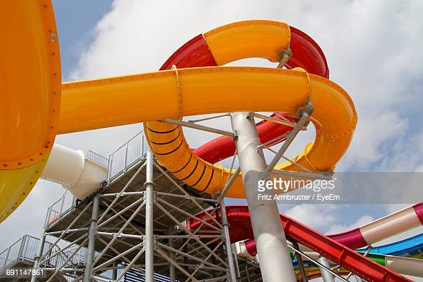 Low Angle View Of Water Slide Against Cloudy Sky