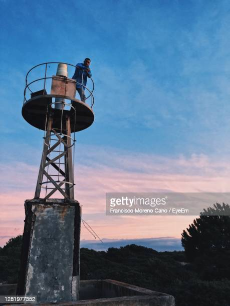 low angle view of water tower against sky during sunset - lookout tower stock pictures, royalty-free photos & images