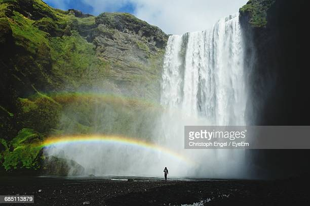Low Angle View Of Waterfall Against Cloudy Sky