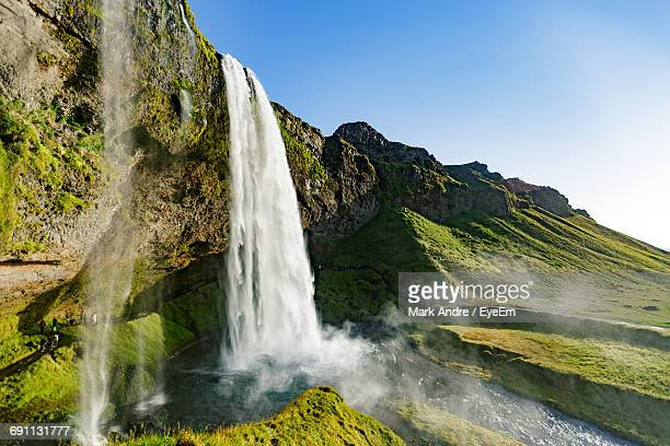 low angle view of waterfall along rocky wall - wasserfall stock-fotos und bilder