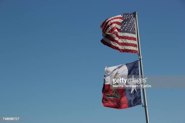 Low Angle View Of Waving Flags On Pole Against Clear Blue Sky