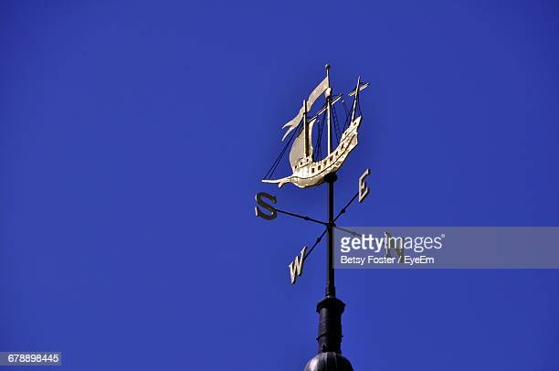 low angle view of weather vane with ship sculpture against clear blue sky - letter s stock pictures, royalty-free photos & images