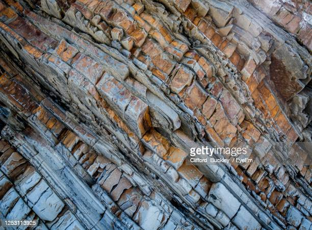 low angle view of weathered cliff - geology stock pictures, royalty-free photos & images