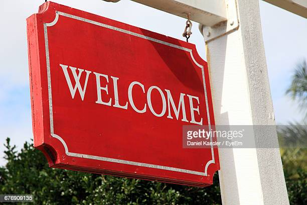 Low Angle View Of Welcome Sign On Wooden Placard Hanging From White Pole