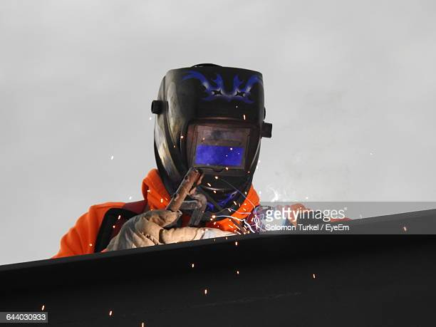 low angle view of welder working at construction site against sky - solomon turkel stock pictures, royalty-free photos & images
