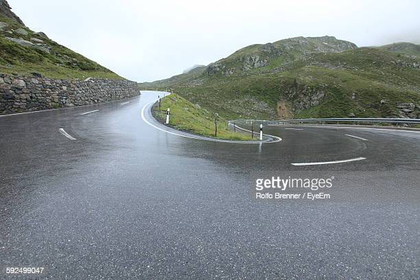 Low Angle View Of Wet Road At Mountain Against Clear Sky