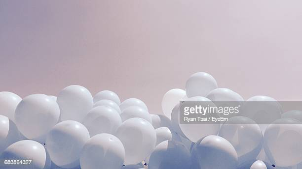 Low Angle View Of White Balloons Against Clear Sky