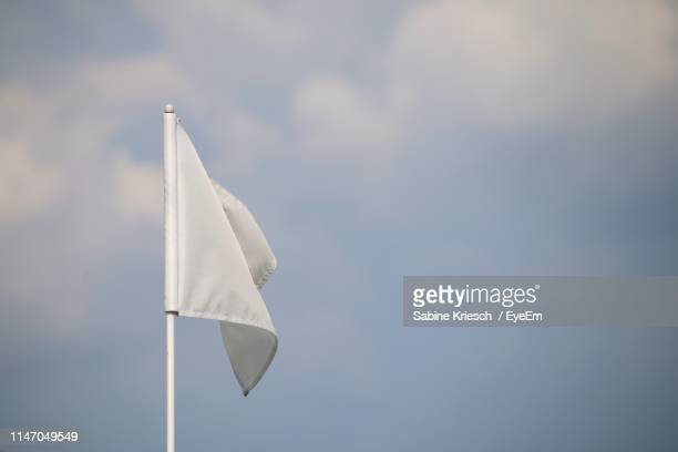 low angle view of white flag against sky - sabine kriesch stock-fotos und bilder