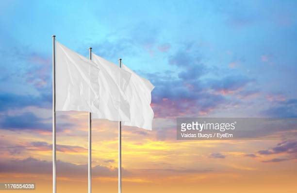low angle view of white flags against sky during sunset - flagpole stock pictures, royalty-free photos & images