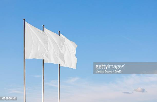 low angle view of white flags waving against blue sky - flag stock pictures, royalty-free photos & images