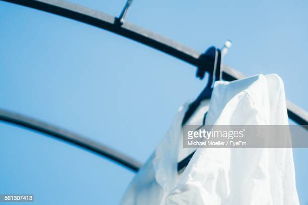 low angle view of white shirt drying on rack against clear blue sky - 乾かす ストックフォトと画像