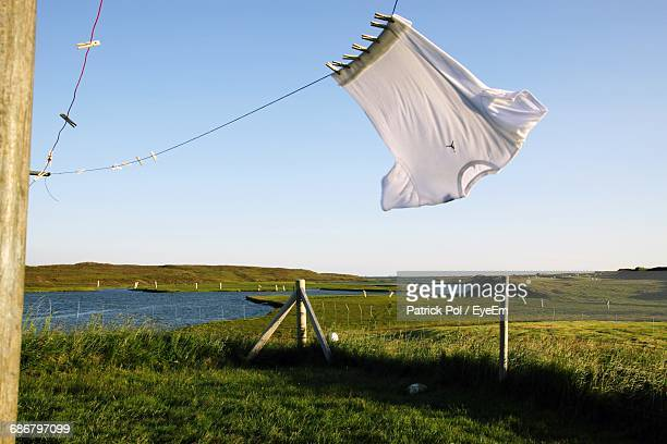 low angle view of white t-shirt hanging on rope against clear sky - white t shirt stock pictures, royalty-free photos & images