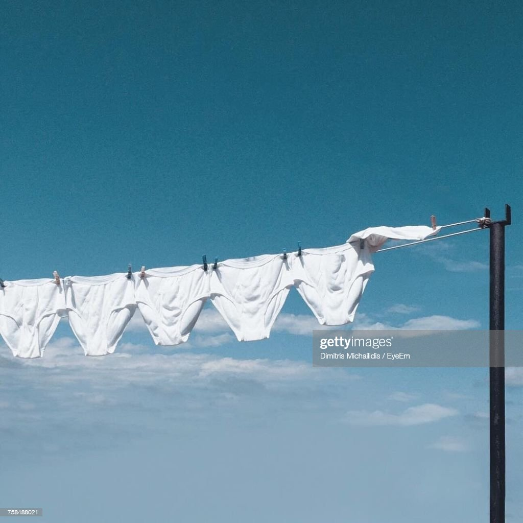 Low Angle View Of White Underwear Hanging On Clothesline : Stock Photo