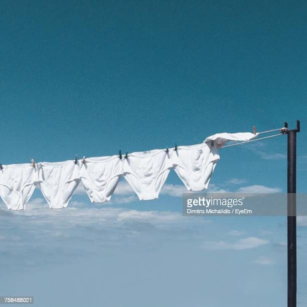 low angle view of white underwear hanging on clothesline - hanging stock photos and pictures