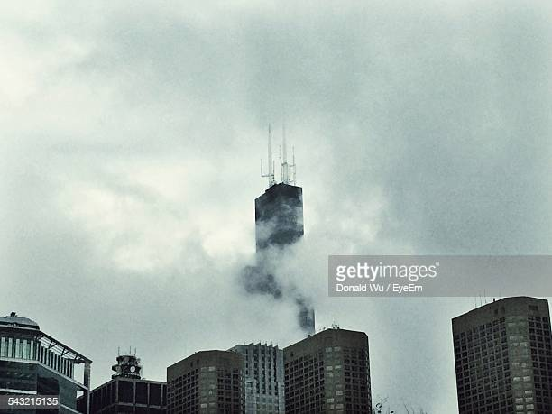 low angle view of willis tower and buildings against cloudy sky - willis tower stock photos and pictures
