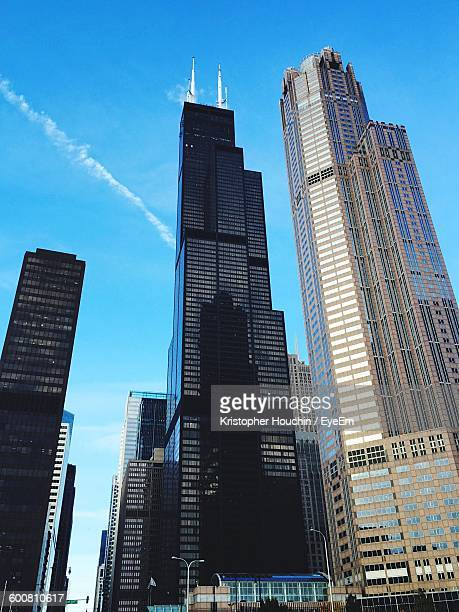 low angle view of willis tower and modern buildings against sky - willis tower stock photos and pictures