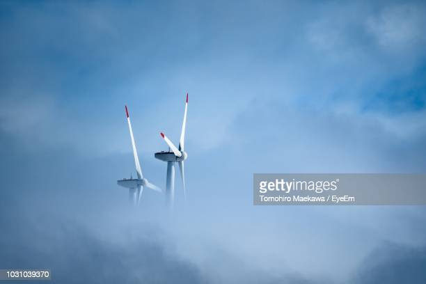 low angle view of windmill against cloudy sky - wind power stock pictures, royalty-free photos & images