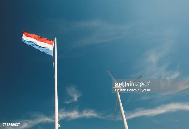 low angle view of windmill and dutch flag against sky - bortes stockfoto's en -beelden