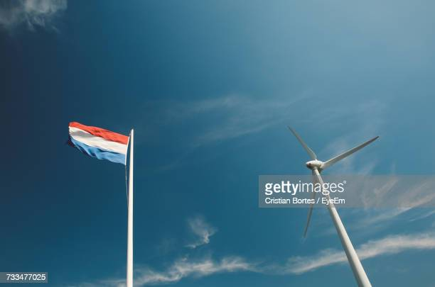 low angle view of windmill by netherland flag against blue sky - bortes stockfoto's en -beelden