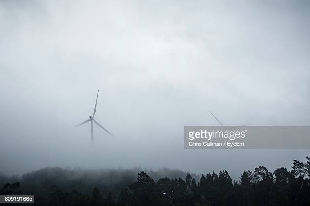 Low Angle View Of Windmill On Field During Foggy Weather