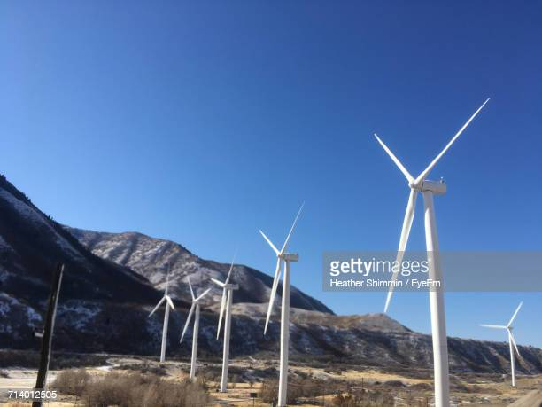 low angle view of windmills against clear blue sky - spanish fork utah stock pictures, royalty-free photos & images