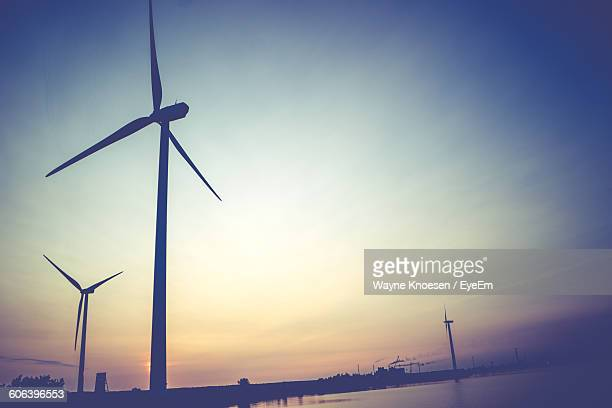 Low Angle View Of Windmills By Lake Against Sky During Sunset