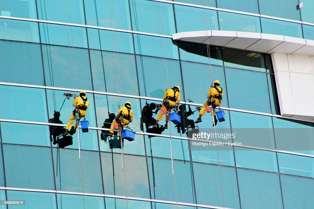 Low Angle View Of Window Cleaners : Stock Photo
