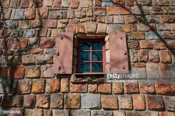 low angle view of window on brick wall of building - karlovy vary stock pictures, royalty-free photos & images