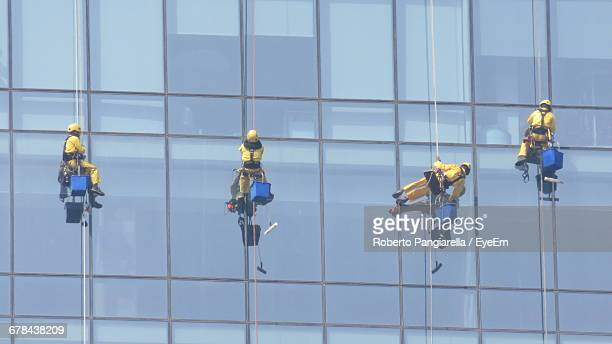 low angle view of window washers cleaning office building - window cleaning stock photos and pictures