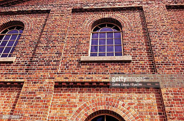Low Angle View Of Windows On Brick Wall