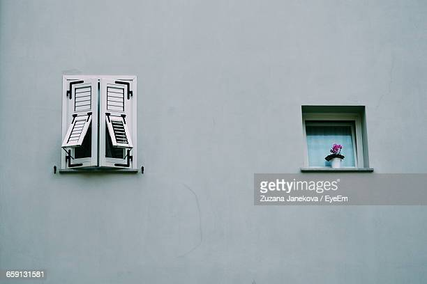 low angle view of windows on wall - zuzana janekova stock pictures, royalty-free photos & images