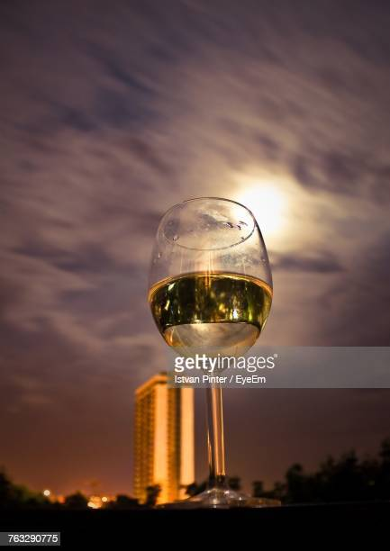 Low Angle View Of Wineglass On Table Against Cloudy Sky At Night