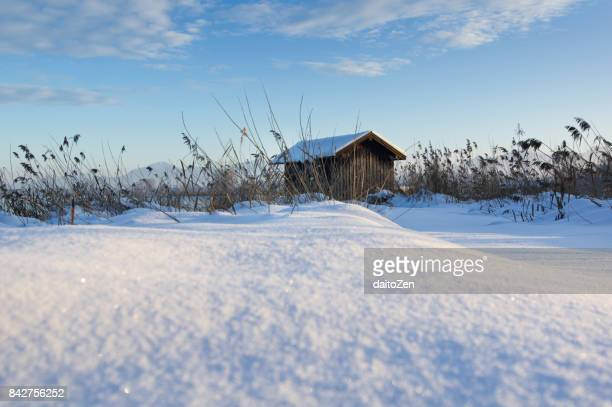 Low angle view of winter landscape at Lake Chiemsee with deep snow and snow-covered boathouse, Chiemgau, Upper Bavaria, Germany