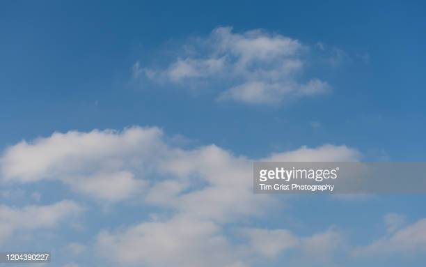 low angle view of wispy white clouds in blue sky - cumulus stock pictures, royalty-free photos & images