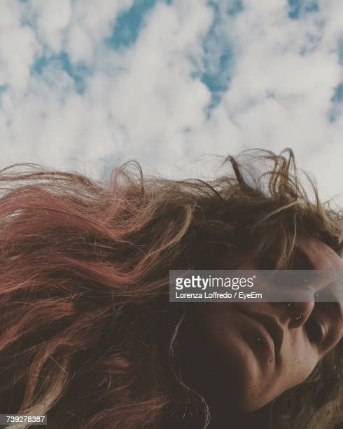 Low Angle View Of Woman Against Cloudy Sky