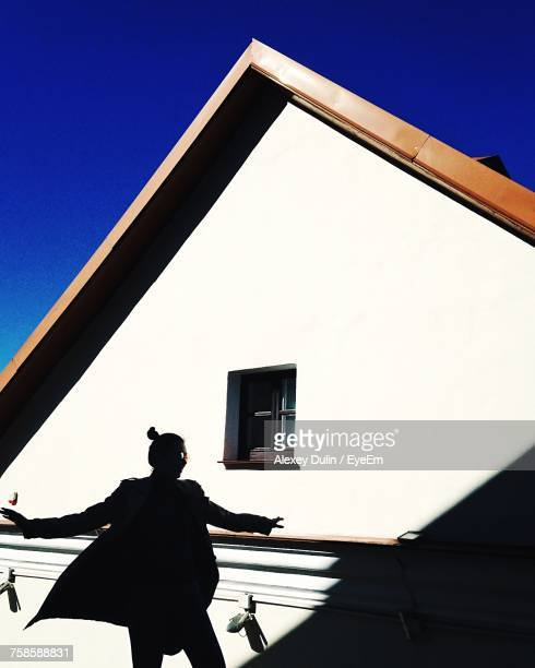 Low Angle View Of Woman Against House