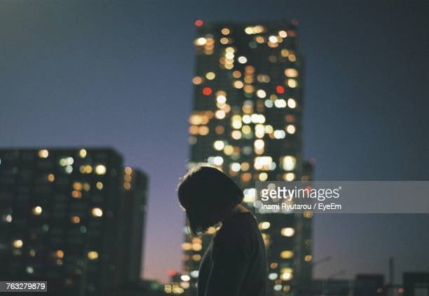 Low Angle View Of Woman Against Illuminated Skyscraper At Night