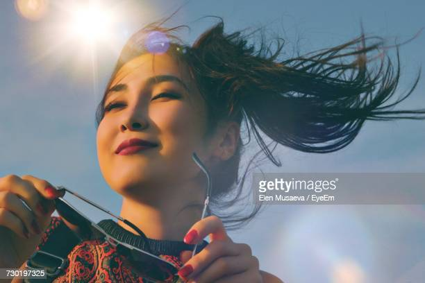 low angle view of woman against sky - tousled hair stock pictures, royalty-free photos & images