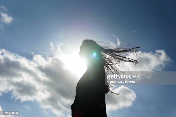 low angle view of woman against sky - tegenlicht stockfoto's en -beelden