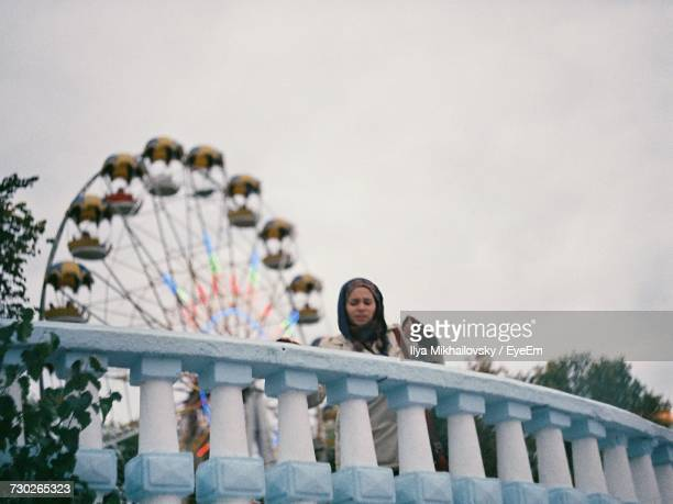 Low Angle View Of Woman And Ferris Wheel Against Clear Sky